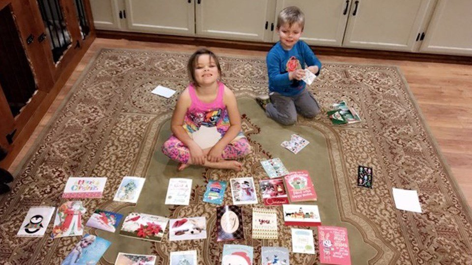 Henry and Alexa, of Arkansas City, open Christmas cards from the community