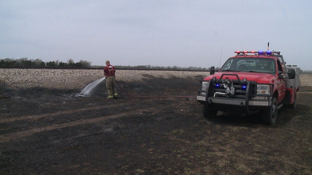 Crews work to extinguish a grass fire near Andale High School on April 11, 2018
