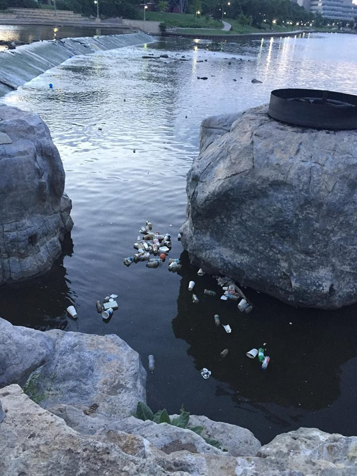 Trash floats in the Arkansas River
