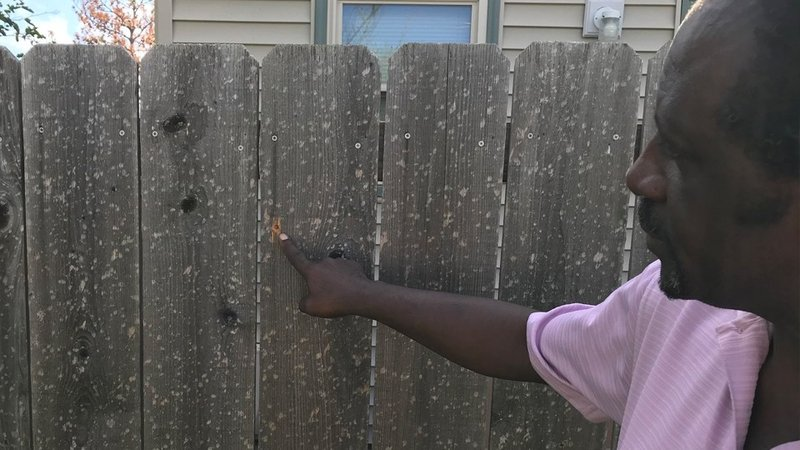 Tyrone Johnson shows where a stray bullet went through a fence before entering his southeast Wichita home and hitting his wife's legs. (Lily Wu/KAKE)