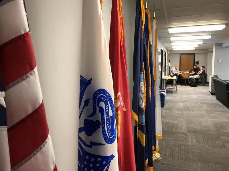 Flags representing all U.S. military branches line the hall at Wichita State's Military and Veteran Services office.  In the background several student veterans are studying.
