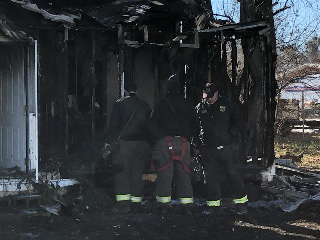 Sedgwick County firefighters check a home for hot spots after clothes falling on a space heater caused an overnight fire.