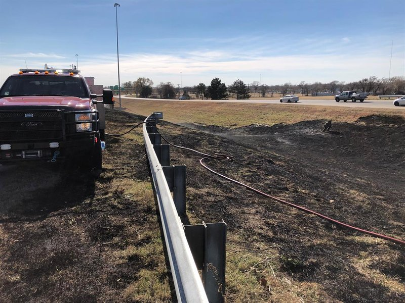 Wichita firefighters battle a grass fire along I-135 on Thanksgiving afternoon.
