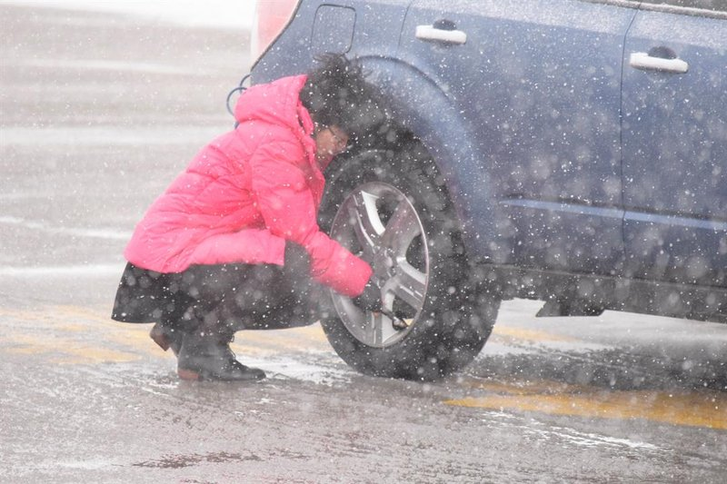 A driver checks her tire pressure at the Towanda rest stop on the Kansas Turnpike Sunday, as the storm blows snow around her.