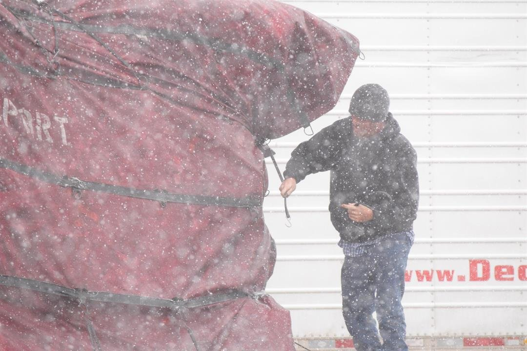 Brian Poole works to secure the tarps covering equipment on the back of his tractor trailer.  Despite the storm, he plans to continue on his way north Sunday.