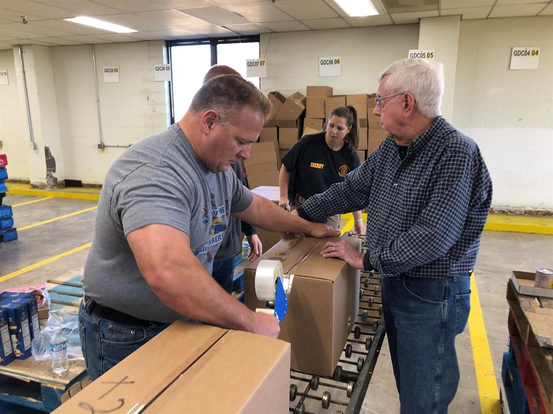 First responders from Sedgwick and Harvey Counties Wednesday, Dec 12, 2018, packing boxes with food for families in need this holiday season.