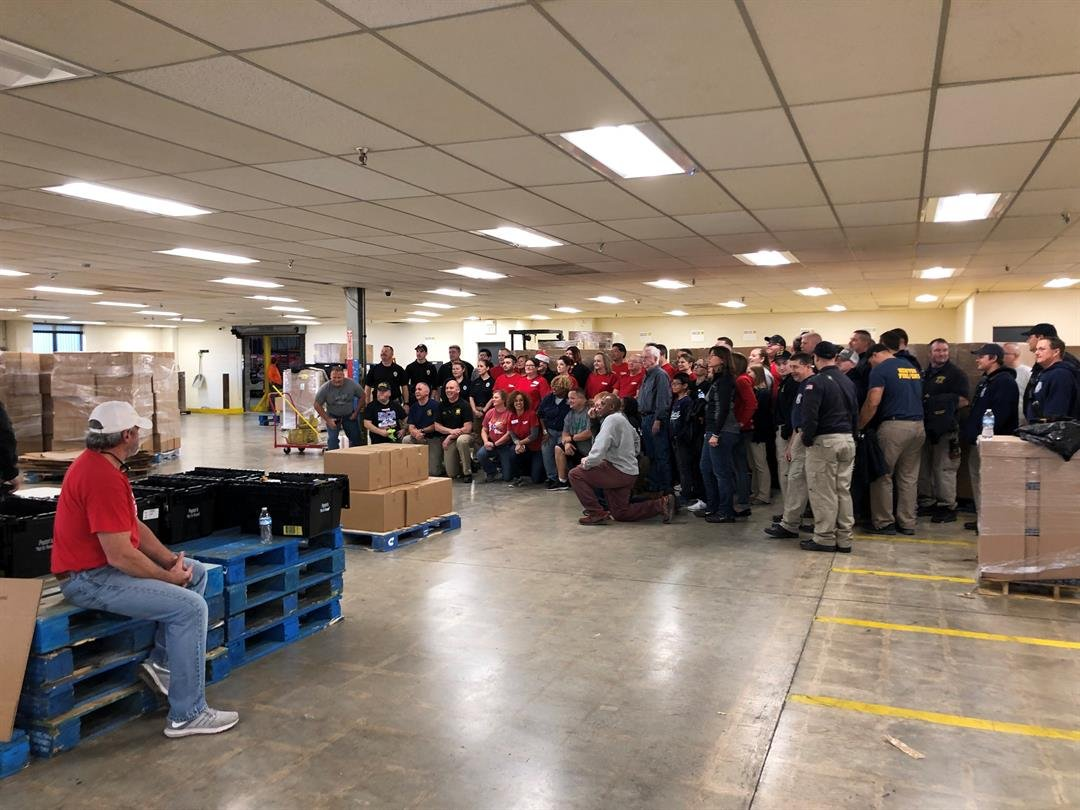 First responders lined up to take a group picture after they finished packing more than 700 boxes of food for families in need in Sedgwick and Harvey Counties Wednesday morning, December 12, 2018.