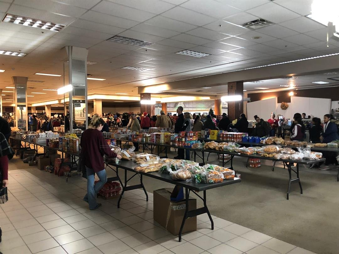 Volunteers keep the tables stocked with donated food items as recipients shop for their favorites for Christmas dinner.