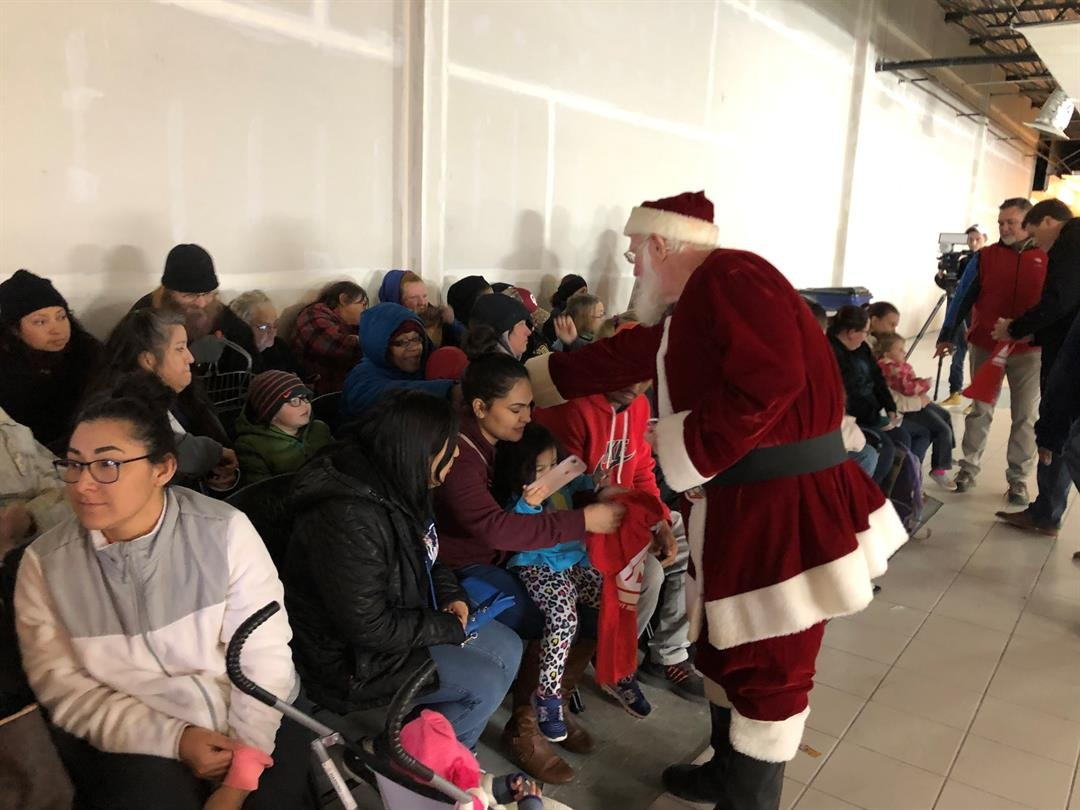Santa handed out candy canes to the kids while they waited their turn to go through the warehouse.