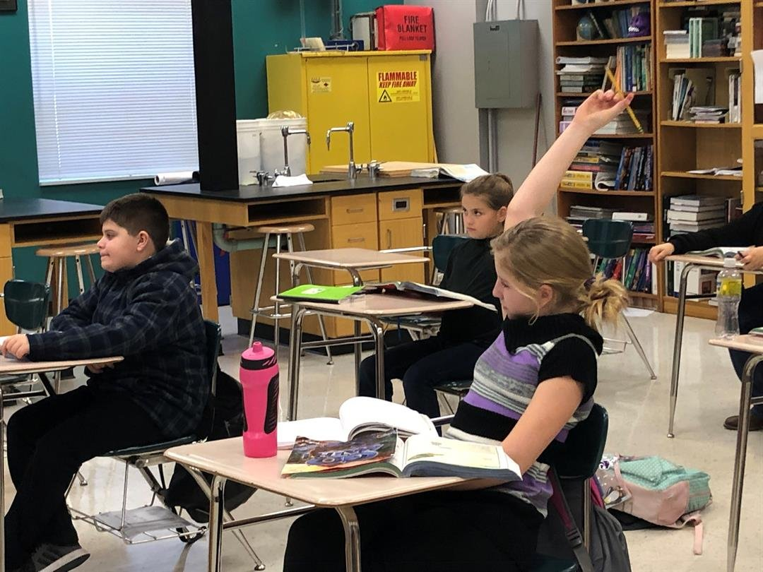 Lack of cell phone service in Longton, Kansas, has residents asking why and how long will the outage last?  One of the biggest concerns is the safety of the town's students.  Here a middle school student raises her and to answer a question, Jan 8, 2019.