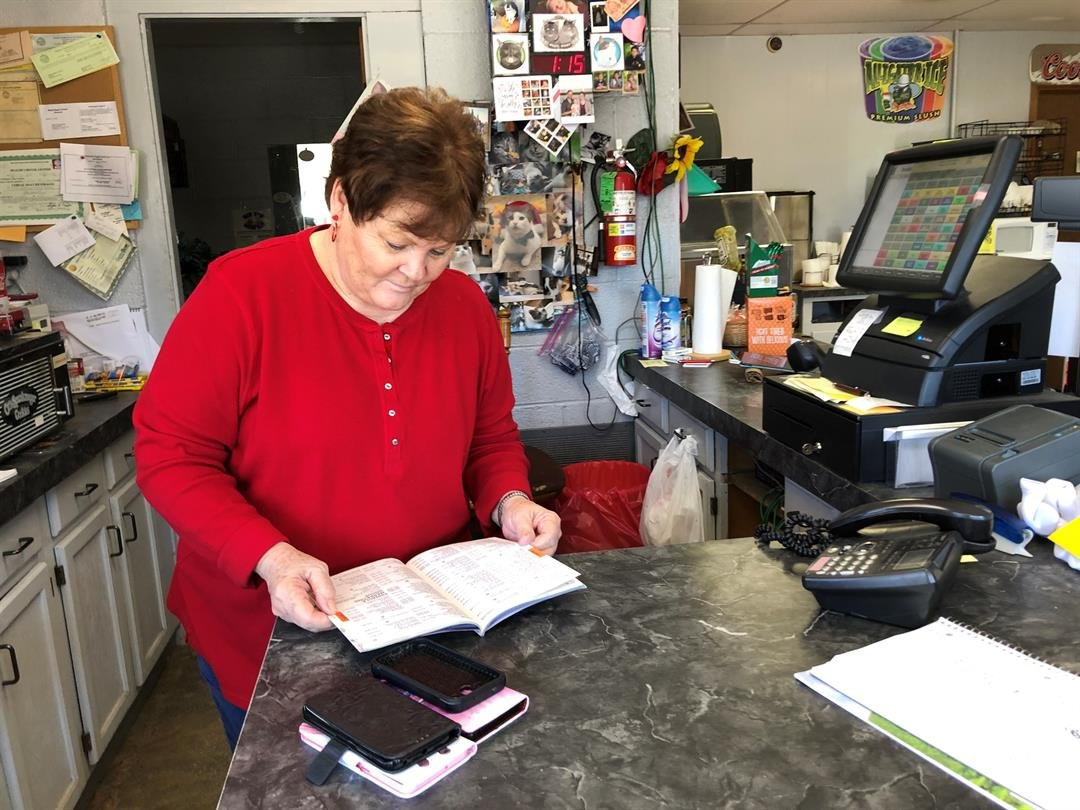 With about 2/3 of Longton residents having cell phones only, the local Mini Mart has become a message center.  Here, clerk Mona Cody looks up a landline number in the phone book on January 8th, 2019.