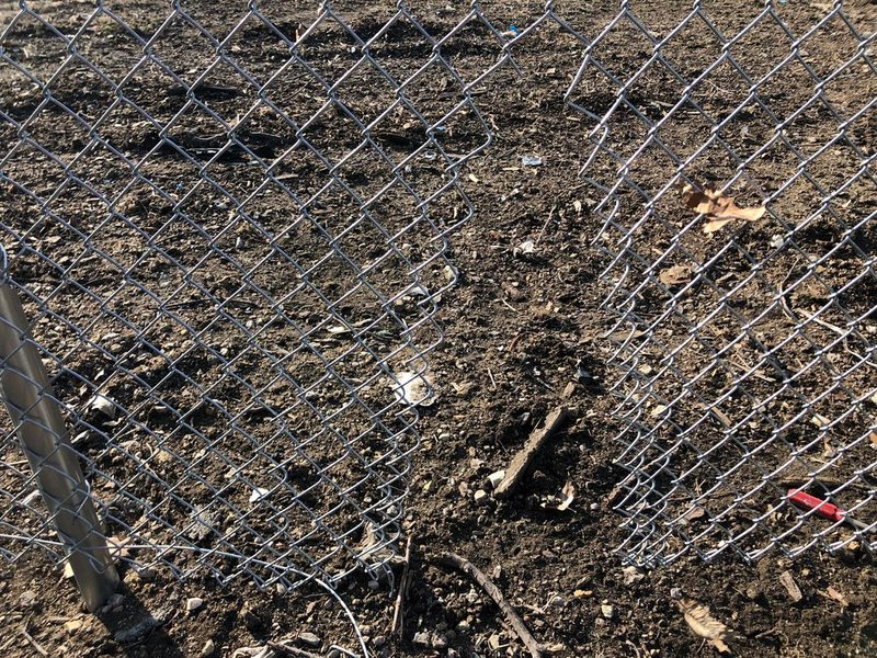 The hole thieves cut into the fence surrounding the League 42 storage facility.