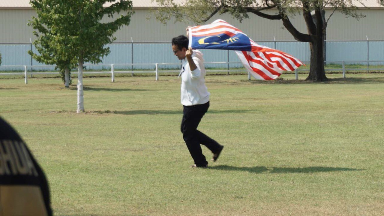 In this photo entered into evidence by Zanial's attorneys, a man is running with the Malaysian national flag during the party at the SBEA lake in September 2017.