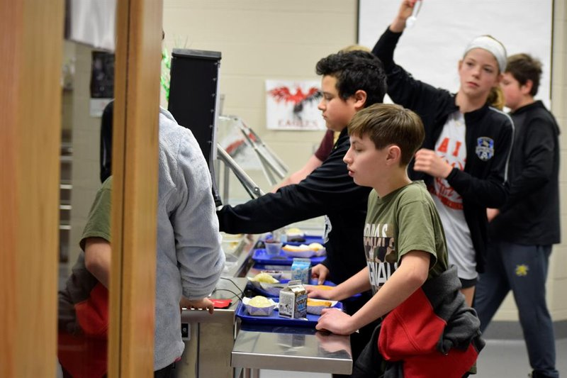 Students at Maize Middle School get their lunches after a daily walk on Tuesday, March 19, 2019.  The last ones back in from the walk struggle to find a place to sit at the crowded tables.