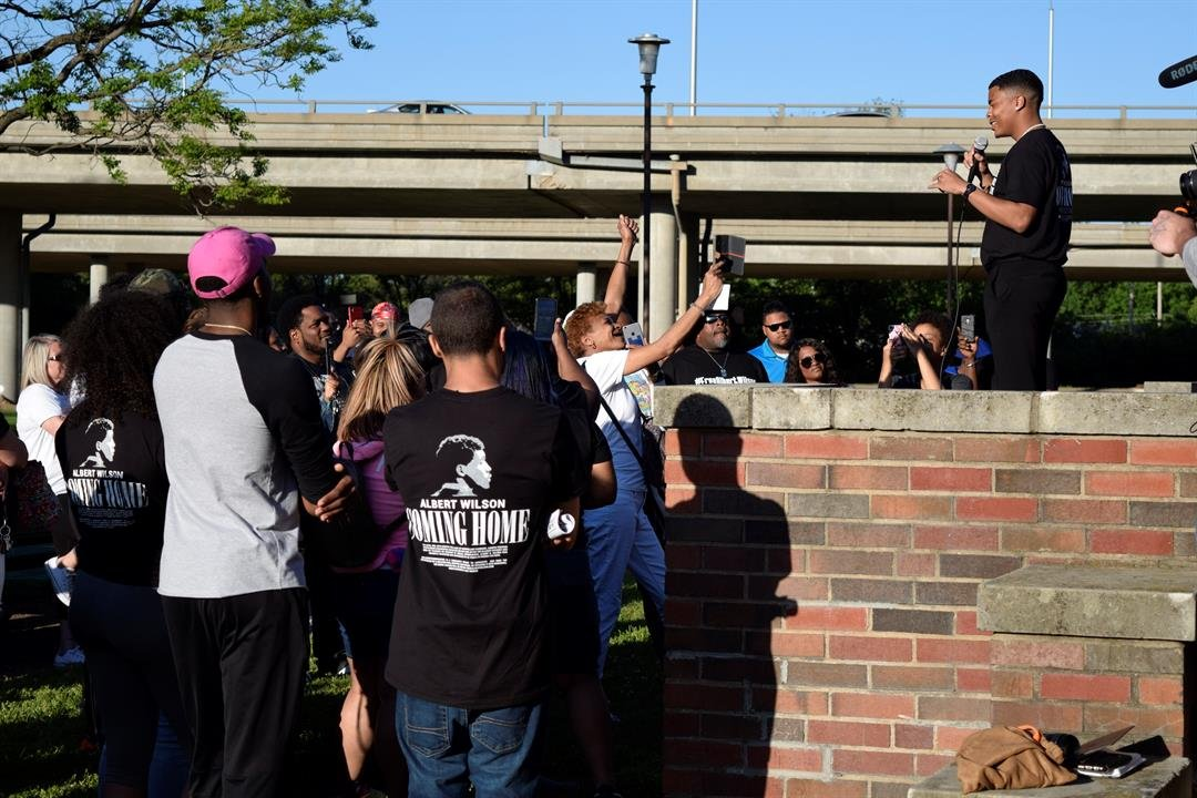 One of Albert Wilson's friends speaks to the crowd at McAdams Park Sunday evening, as his mother stands in front of the stage holding her phone up to livestream the event for Wilson.
