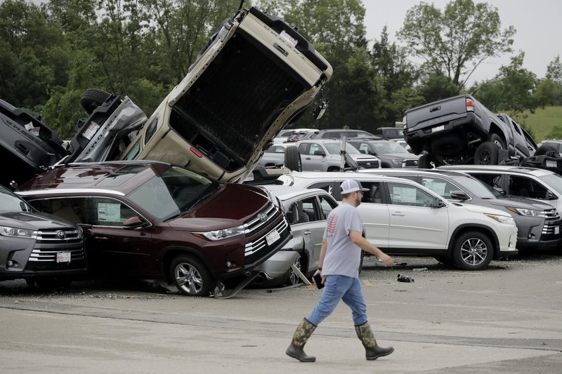 A worker walks past tornado-damaged Toyotas at a dealership in Jefferson City, Mo.  (AP Photo/Charlie Riedel)