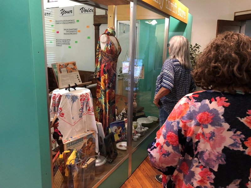 Visitors to TKAAM on Wednesday browsing the exhibits on racially charged items donated to local thrift stores.