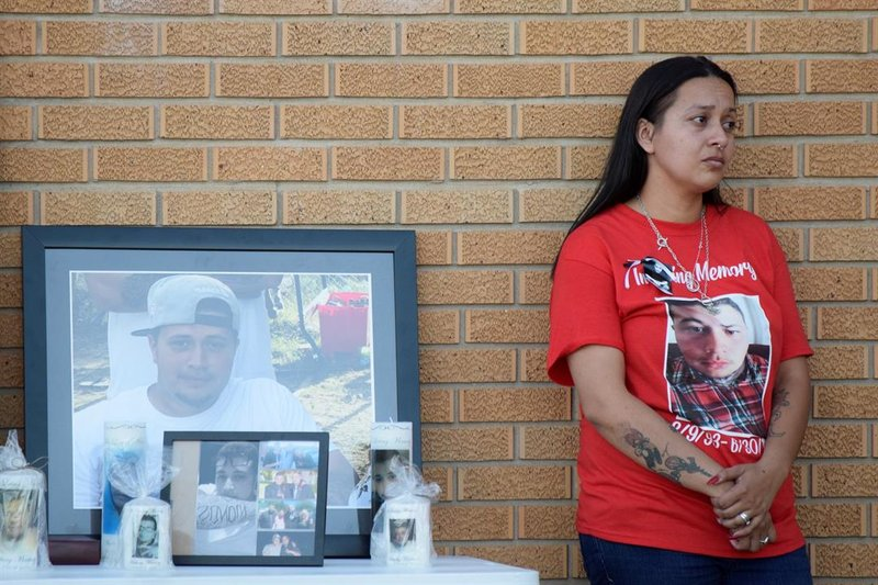 Vanessa Ayala stands next to photos of her husband, Anthony Martinez, killed a year ago Sunday in a shooting.   She's at a vigil in honor of him and other victims of gun violence on June 30, 2019.