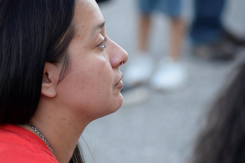 Vanessa Ayala watches a Christian rapper perform at a vigil honoring her husband and other victims of gun violence. Christian rap was her husband's favorite music.
