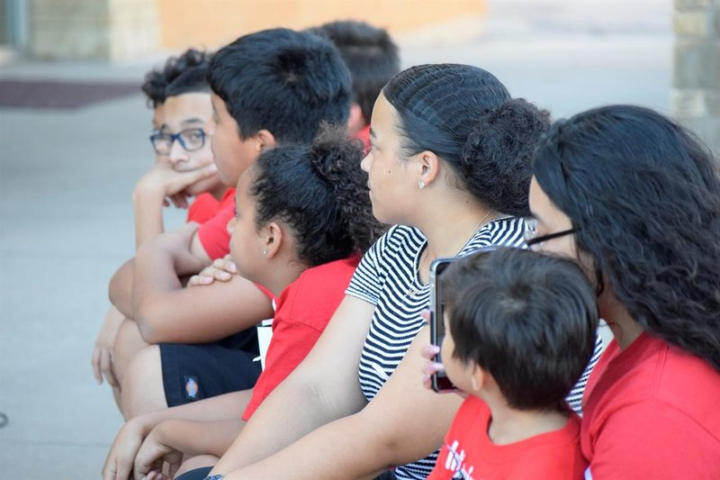 Several children, including Anthony Martinez' kids, watch on as Vanessa Ayala speaks about their loss, frustration, anger, and hopes.