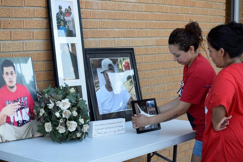Friends of the Martinez family putting up photos of Anthony Martinez in happier times at a vigil honoring him and other victims of gun violence on June 30, 2019.
