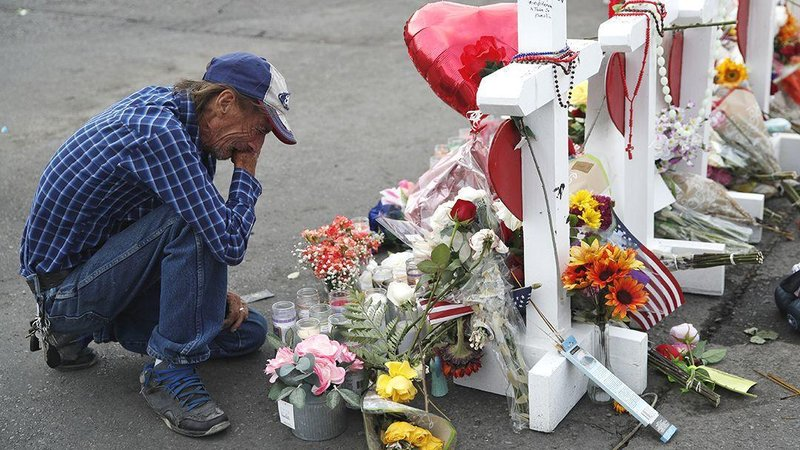 Antonio Basco cries beside a cross at a makeshift memorial near the scene of a mass shooting Tuesday, Aug. 6, 2019, in El Paso, Texas. (AP Photo/John Locher)