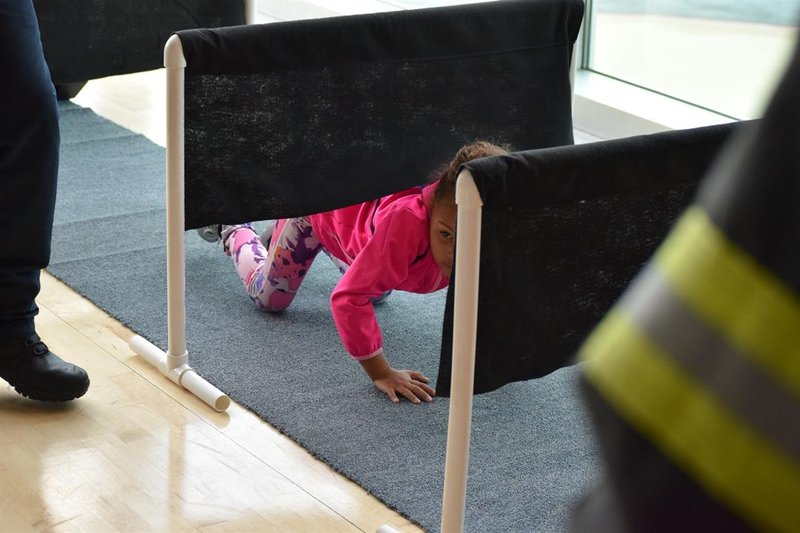 "Another Wichita elementary student practices crawling low to the ground while checking to be sure the ""door"" to the ""bedroom"" is closed before escaping out the ""window""."