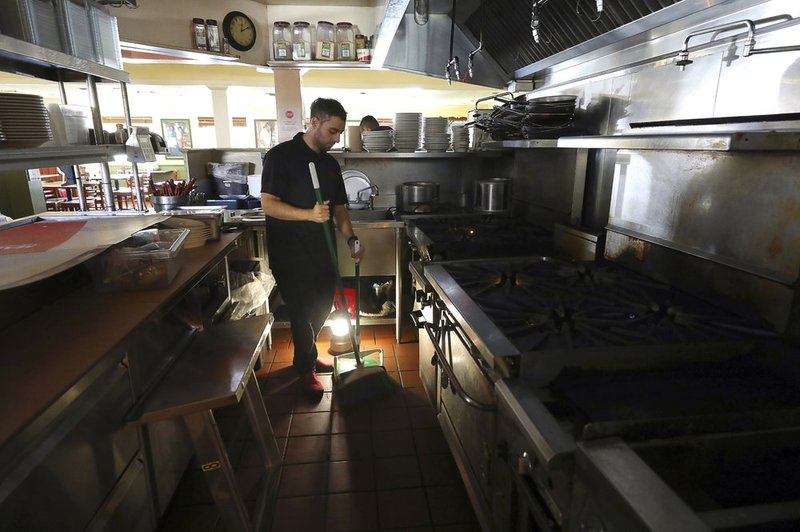 Salvador Espinosa sweeps in the kitchen of a Mary's Pizza Shack restaurant during a Pacific Gas and Electric Co. power shutdown in Santa Rosa, Calif., Thursday, Oct. 10, 2019. (AP)