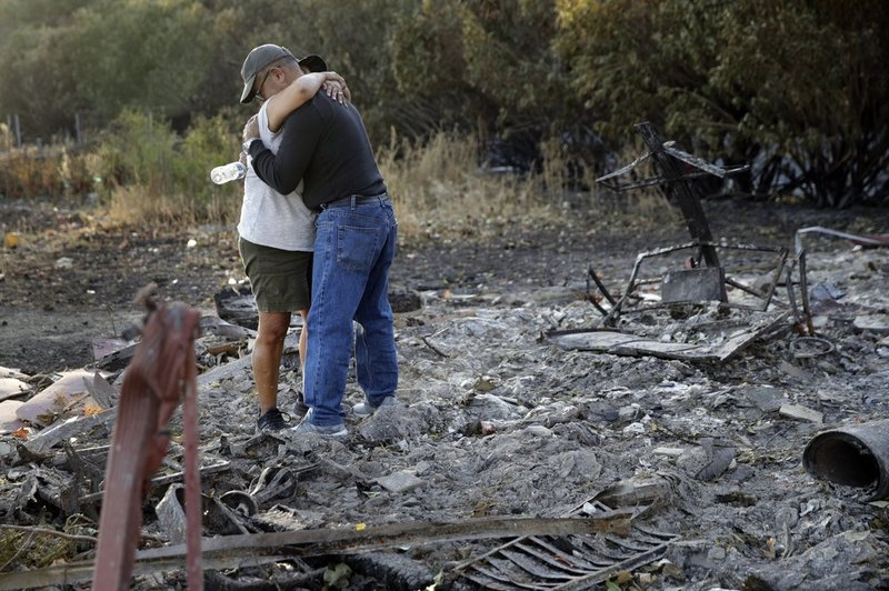 Justo and Bernadette Laos hug while looking through the charred remains of the home they rented that was destroyed by the Kincade Fire near Geyserville, Calif., Thursday, Oct. 31, 2019. The fire started last week near the town of Geyserville