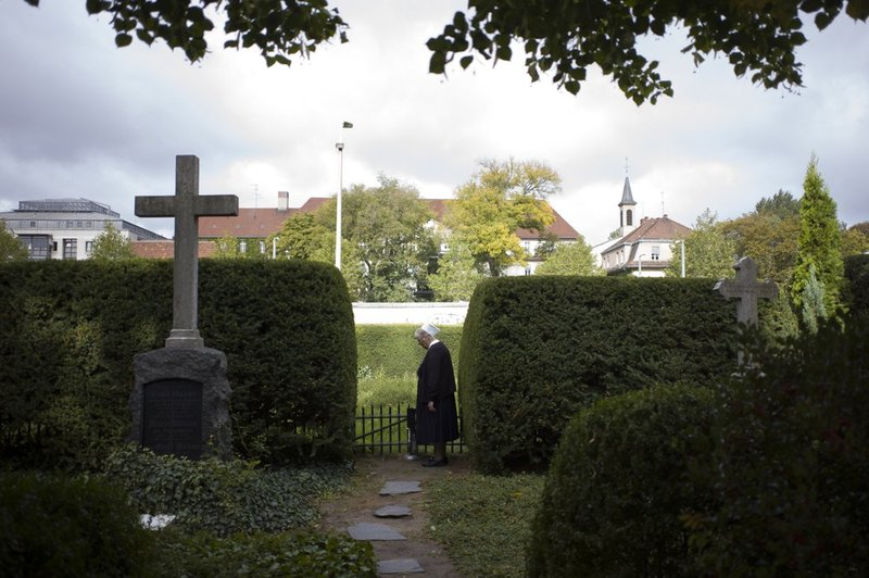 In this Sept. 18, 2019, photo, Sister Brigitte Queisser of the Lutheran Lazarus Order stands near graves of the Lazarus sisters during an interview with The Associated Press in Berlin.