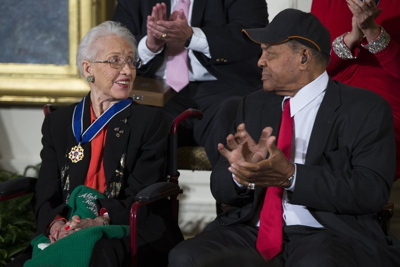 In a Nov. 24, 2015 file photo, Willie Mays, right, applauds NASA mathematician Katherine Johnson, after she received the Presidential Medal of Freedom from President Barack Obama during a ceremony in the East Room of the White House.