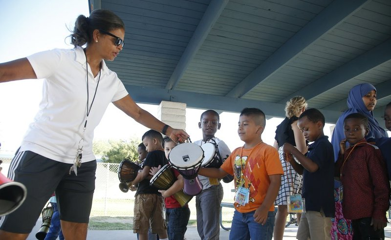 eacher Linda Patterson, left, hands a drum to Roberto Gomez Ruiz, middle, as his classmates look on at Valencia Newcomer School Thursday, Oct. 17, 2019, in Phoenix. Children from around the world who are learning the English skills